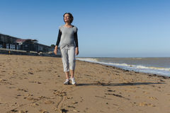 Mature woman walking on the beach Royalty Free Stock Photo