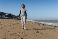 Mature woman walking on the beach. Mature woman enjoying a walk on the beach Royalty Free Stock Photo