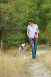 Mature woman is walking a dalmatian dog on a leash  in nature en Royalty Free Stock Photos