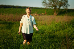 Mature woman walking in a field stock photo