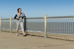 Mature woman walking to squash by the beach Stock Images