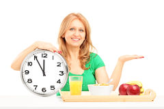 Mature woman with wall clock and fruit and vegetables in a woode Stock Photos