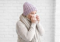 Mature woman in warm clothes suffering from cold on brick background Royalty Free Stock Photo