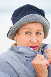 Mature woman in warm jumper in cold season. Portrait attractive mature woman feeling cold and unhappy frosty, wearing jumper and hat to keep warm outside Royalty Free Stock Image