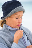 Mature woman in warm jumper in cold weather. Portrait attractive mature woman feeling cold and frosty, wearing jumper and hat to keep warm outside, blurred Stock Photos