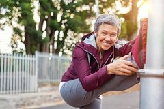 Mature woman warming up before jogging stock images