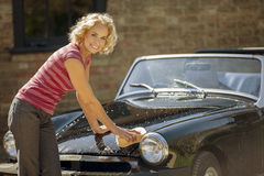 A mature woman washing a classic sports car Royalty Free Stock Images