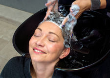 Mature woman washing hair Royalty Free Stock Image