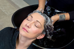 Mature woman washing hair Royalty Free Stock Photos
