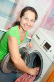Mature woman with washing machine. At her home Royalty Free Stock Images