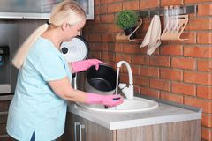 Mature woman washing multi cooker in kitchen sink. Mature woman washing modern multi cooker in kitchen sink royalty free stock photo