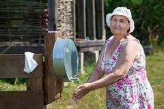 Mature woman washs her hands at country residence Stock Photo