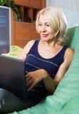 Mature woman watching soap show Stock Photo