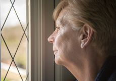 Mature woman watching through a window stock images