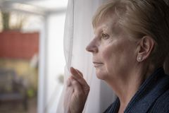 Mature woman watching through a window stock photography