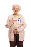 Mature woman wearing an award ribbon and pointing. Isolated on white background Royalty Free Stock Photos