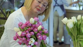 Mature woman hold bouquet of roses and tulips. Mature woman wearing eyeglasses hold beautiful bouquet of roses and tulips. Portrait of attractive senior woman stock video footage