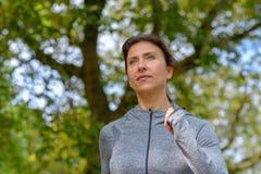 Mature woman wearing grey jacket and jogging royalty free stock image