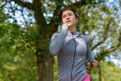 Mature woman wearing grey jacket and jogging royalty free stock photography