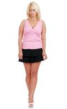 Mature woman wearing short skirt and pink top. Isolated mature woman wearing short skirt and pink top on white background Stock Photography