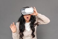 Freestyle. Mature lady in virtual reality headset standing isolated on grey playing surprised stock image