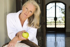 Mature woman wearing white bath robe, holding green apple, smiling, portrait Stock Images