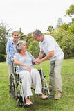 Mature woman in wheelchair with husband and daughter Stock Images