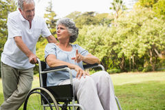Mature woman in wheelchair speaking with partner. Mature women in wheelchair speaking with partner in the park on sunny day Royalty Free Stock Images