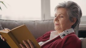 Mature woman in white blouse reading book at home lying on sofa. Concept of: domestic life, free time, retirement, knowledge, relaxing. Portrait stock footage
