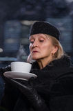 Mature woman with white cup in hands. Stock Photo