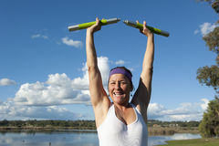 Mature Woman in Winner Pose. A mature woman exercising with weights at a lake in a winner pose, stretching her arms in the air Royalty Free Stock Photos