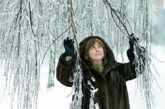 Mature woman in a winter forest Royalty Free Stock Image