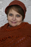 Mature woman in winter hat and knitted orange scarf Stock Photography