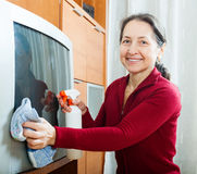 Mature woman wiping the dust  on TV Stock Photos