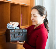 Mature woman wiping dust from wooden chest Royalty Free Stock Photo