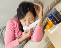 Mature woman wiping her nose with tissue while lying in bed Stock Photo