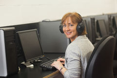 Mature woman working on computer while listening to music Stock Images