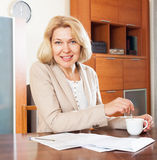 Mature woman working with  documents at table in home Royalty Free Stock Photography