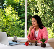 Mature woman working from home in morning attire with bright day Royalty Free Stock Image
