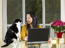 Mature woman working at home wth family looking at her Stock Images