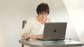 Mature woman working with laptop. She is dressed in a business suit and strict glasses stock footage