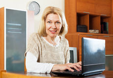 Mature  woman working at laptop in the office. Mature business woman working at laptop in the office Stock Images