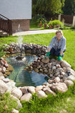 Mature woman works around pond in her garden Stock Photography