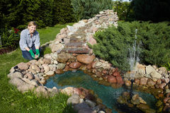 Mature woman works around pond in her garden Royalty Free Stock Photography