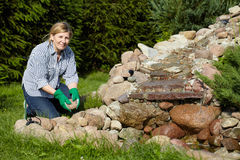 Mature woman works around pond in her garden Royalty Free Stock Image