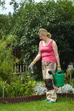 Mature woman works in her garden Stock Photo