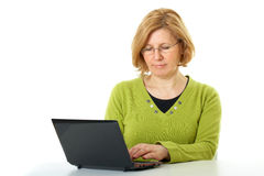 Mature woman works on her laptop,  Royalty Free Stock Images