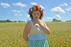 The mature woman with a wreath on the head smells flowers agains. T the background of the buckwheat field Royalty Free Stock Photography