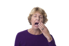 Mature woman yawning. Mature woman covering mouth as she yawns widely royalty free stock photos