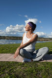 Mature Woman Yoga. A mature woman stretching her body with yoga exercises at a lake Royalty Free Stock Photography